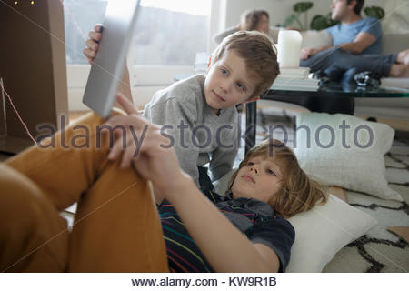 Brothers playing with digital tablet in living room - Stock Photo