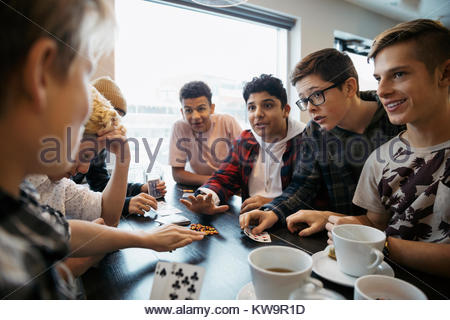 Tween boy friends playing cards and drinking coffee at cafe table - Stock Photo