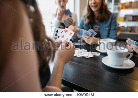 Tween girl friends playing cards and drinking coffee in cafe - Stock Photo