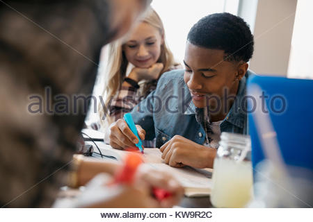 High school boy student studying,highlighting textbook in cafe - Stock Photo