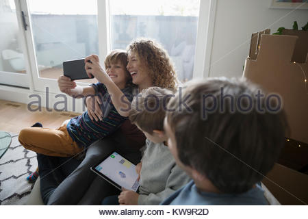 Happy mother and son taking selfie with camera phone on sofa - Stock Photo