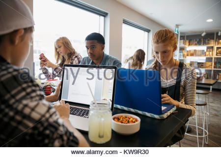 High school students studying at laptops in cafe - Stock Photo