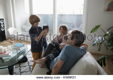 Son with camera phone photographing family relaxing on sofa - Stock Photo