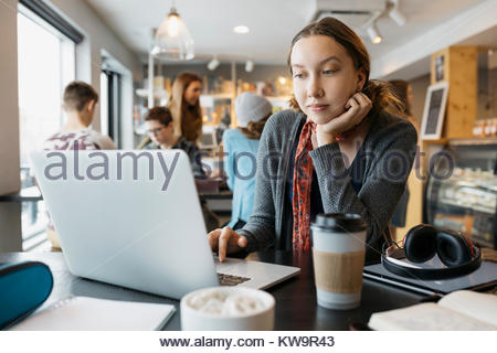 Serious,focused high school girl student studying at laptop,drinking coffee in cafe - Stock Photo