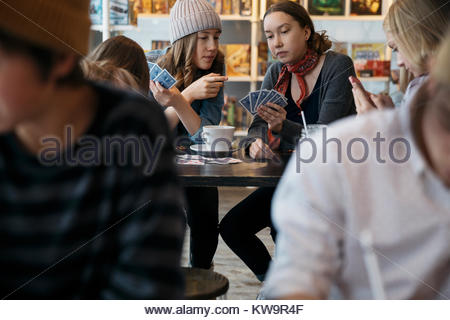 Tween girl friends playing cards at cafe table - Stock Photo