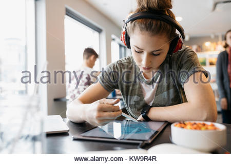 High school girl student with headphones using stylus,drawing on digital tablet in cafe - Stock Photo