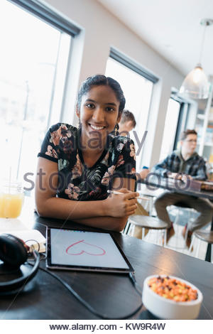 Portrait confident Indian tween girl drawing heart-shape with stylus on digital tablet in cafe - Stock Photo