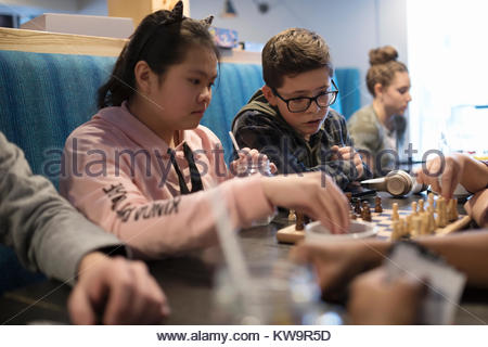 Tween friends playing chess at cafe table - Stock Photo