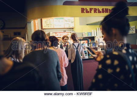 Tweens waiting in queue at refreshments concession stand in movie theater - Stock Photo