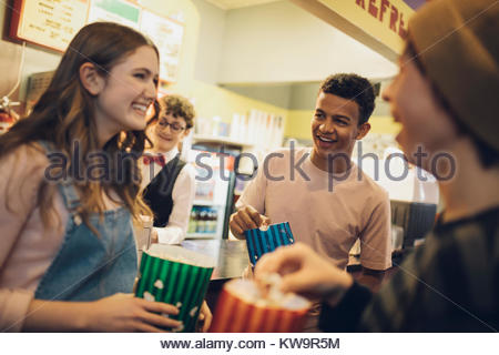 Smiling tween friends with popcorn at refreshments concession stand movie theater - Stock Photo