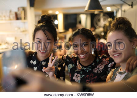 Smiling tween girl friends taking selfie with camera phone in cafe - Stock Photo