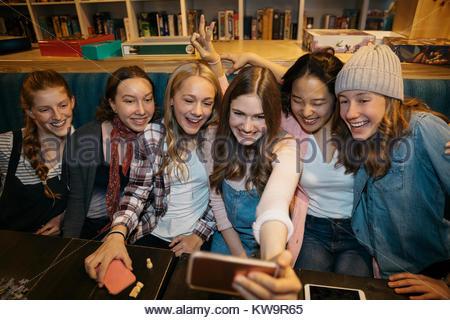Tween girl friends taking selfie with smart phone in cafe - Stock Photo