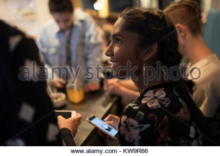 Smiling Indian tween girl texting with smart phone,hanging out at cafe table - Stock Photo