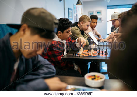 Tween boy friends playing chess at cafe table - Stock Photo