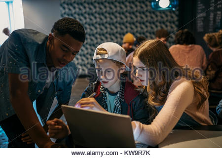 Focused high school students studying at laptop in cafe - Stock Photo