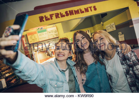 Smiling,enthusiastic Caucasian tween girl friends taking selfie with camera phone in movie theater - Stock Photo