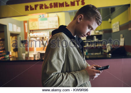 Caucasian tween boy texting with smart phone at refreshments concession stand in movie theater lobby - Stock Photo