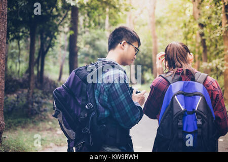 Asian Group of young people Hiking with friends backpacks walking together and looking map and taking photo camera - Stock Photo
