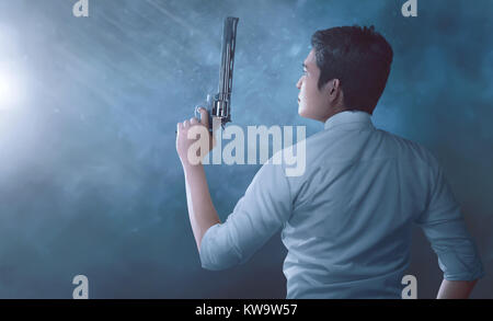 Young asian man police with uniform holding guns in his hands over dark backgronud - Stock Photo