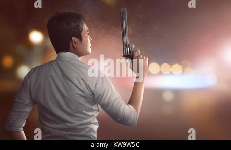Back view of asian man in police unifrom holding guns with blurred light background - Stock Photo