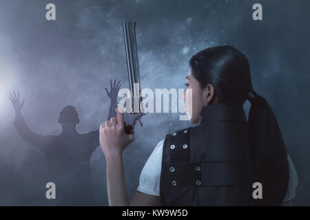 Young asian woman in a police uniform with pistol on her hands on dark background - Stock Photo