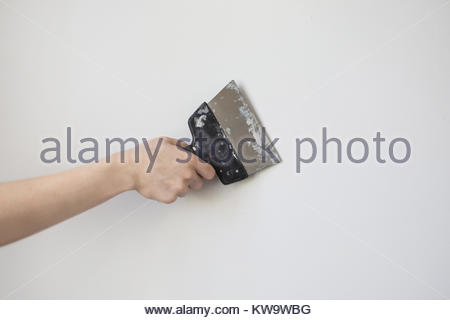 Trowel in man's hand on a background of a white wall. Dirty tools for repair. Tool for getting rid of the wallpaper. - Stock Photo
