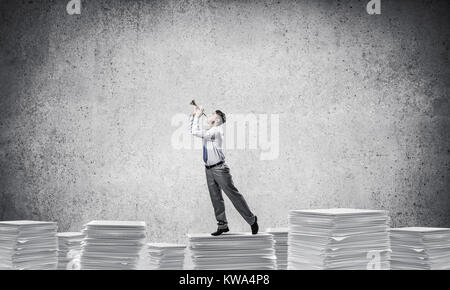 Businessman playing fife while standing on pile of documents with grey background. Mixed media. - Stock Photo