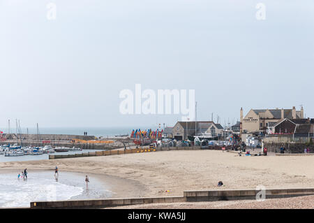 View across the beach towards The Cobb and harbour in Lyme Regis, Dorset, England, UK. - Stock Photo