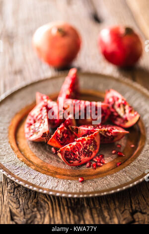 Pomegranate. Pieces of frest pomegranate on plate. - Stock Photo