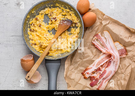 Ham and eggs. Scrambled eggs with bacon in ceramic pan. - Stock Photo