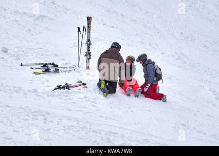 WINTERBERG, GERMANY - FEBRUARY 16, 2017: Woman sitting on a ski slope with injured leg being taken care of at Ski - Stock Photo