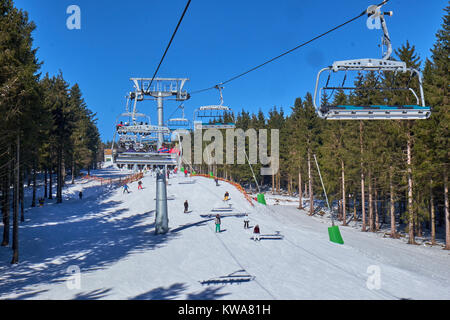 WINTERBERG, GERMANY - FEBRUARY 14, 2017: People on skis seen from up high in a chairlift at Ski Carousel Winterberg - Stock Photo