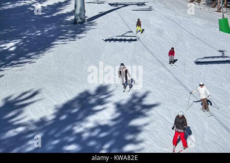 WINTERBERG, GERMANY - FEBRUARY 14, 2017: Group of skiers running under a chairlift at Ski Carousel Winterberg - Stock Photo