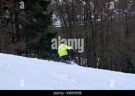 WINTERBERG, GERMANY - FEBRUARY 16, 2017: Man in fluorescent jacket taking a swing on a piste at Ski Carousel Winterberg - Stock Photo