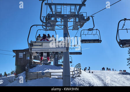 WINTERBERG, GERMANY - FEBRUARY 14, 2017: People sitting up high above the pistes in a chairlift at Ski Carousel - Stock Photo