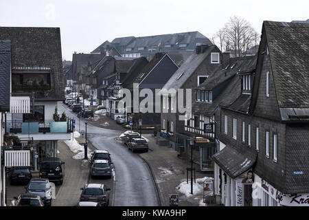 WINTERBERG, GERMANY - FEBRUARY 16, 2017: Narrow street in Winterberg with slate decorated town villas on both sides - Stock Photo