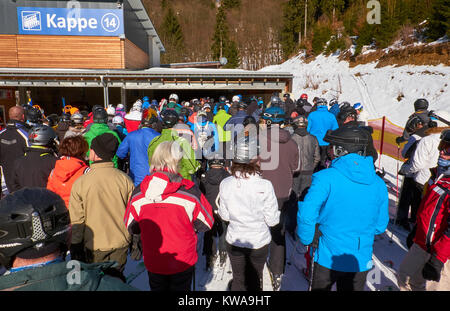 WINTERBERG, GERMANY - FEBRUARY 14, 2017: Skiers standing waiting in line to get to a chairlift for getting to the - Stock Photo