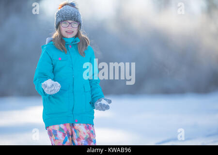 Happy young Pre-Teen girl in warm clothing  playing with snow. - Stock Photo