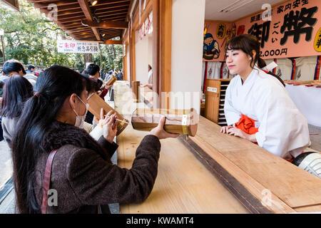 Japan, Nishinomiya, shrine. New Year. People buying omikuji, paper fortune slips, from shrine maidens, Miko, at - Stock Photo