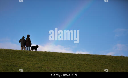 Norddeich, Germany. 02nd Dec, 2018. Two strollers with their dog walk along the embankment with a rainbow in the - Stock Photo