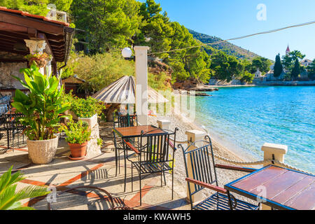 Tables with chairs of small coastal restaurant on beach in Bol town, Brac island, Croatia - Stock Photo