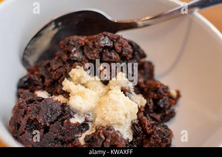 A portion of Christmas pudding with some brandy butter in a bowl - Stock Photo