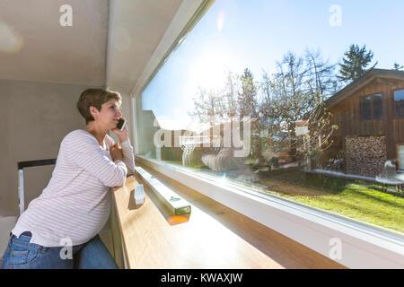 Schwangere Frau vor Fenster mit Unterlagen auf der Baustelle im neuen Haus - Stock Photo