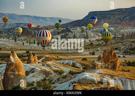 Fairy chimneys, mesa and hot air balloons, near Goreme, Cappadocia, Turkey - Stock Photo