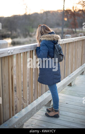 woman in winter coat looking over railing of wooden foot bridge in forest at sunset - Stock Photo
