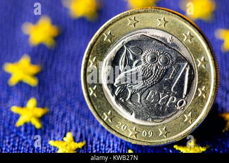 Greek euro-coin one on EU flag, Griechische Ein-Euro-M?nze auf EU-Fahne, Griechische Ein-Euro-Muenze auf EU-Fahne - Stock Photo