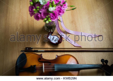 Wedding rings in the red box, a violin and bow, wedding flowers, wedding bouquet of beautiful pink roses and white - Stock Photo