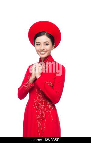 Young vietnamese woman in Ao Dai Dress with praying gesture wishing you good luck - Stock Photo
