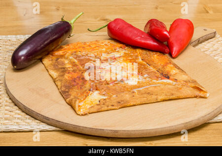Delicious crepe with eggplant and cheese served on a wooden board - Stock Photo