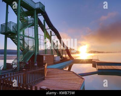 High steel tower with  sliding track on lake beach. Cold autumn morning with misty water level. End of season in - Stock Photo